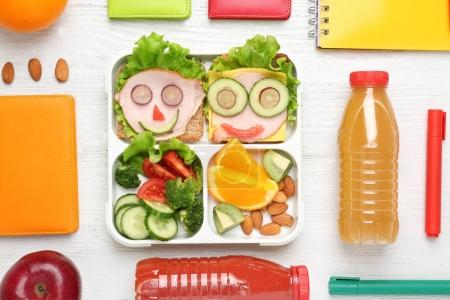 Funny sandwiches in lunch box and stationery on white wooden background