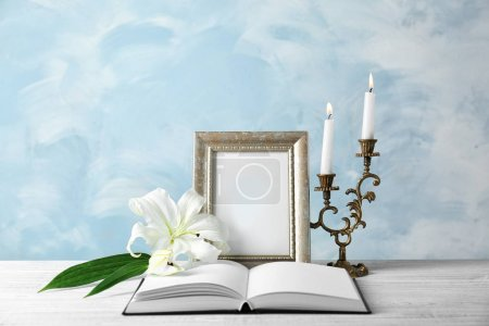 frame, candles, opened book and lily