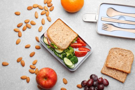 Lunch box with delicious food, fruits and almond on light textured background