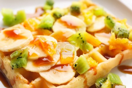 Photo for Delicious waffle with fruits and syrup on white plate, close up - Royalty Free Image