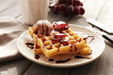 Photo for Tasty waffles with delicious grape, ice-cream and syrup on white plate - Royalty Free Image