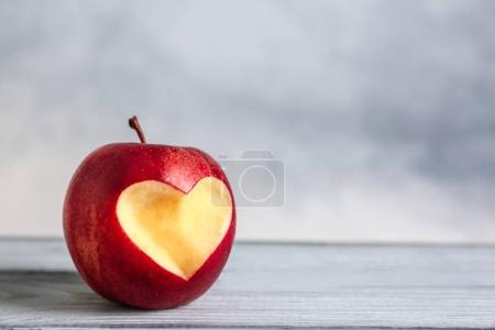 Photo for Fresh red apple with heart-shaped cut out  on wooden table - Royalty Free Image