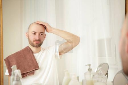 Photo pour Notion de perte de cheveux. Jeune bel homme regardant miroir - image libre de droit