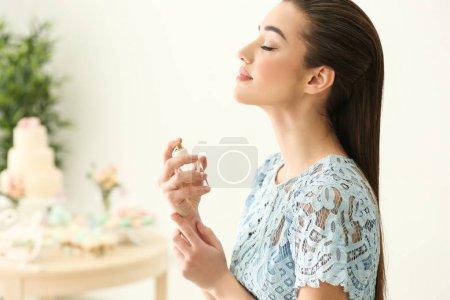Photo pour Belle jeune femme avec une bouteille de parfum à domicile - image libre de droit