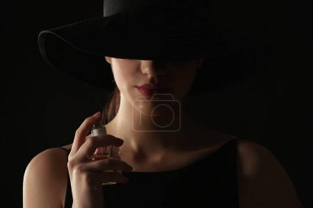 Beautiful young woman with bottle of perfume