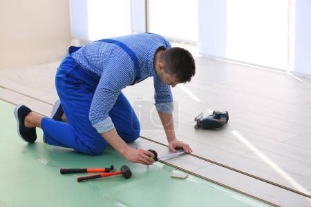 worker installing laminate flooring