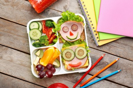 Funny sandwiches in lunch box and colorful stationery on wooden background