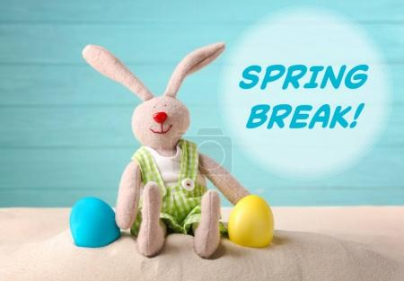 Photo for Spring break concept. Colorful Easter eggs and toy bunny on sand - Royalty Free Image
