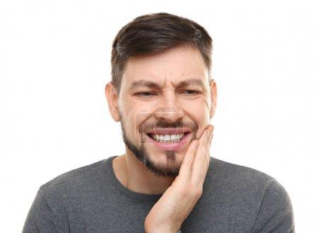 Photo pour Beau homme souffrant de maux de dents sur fond blanc - image libre de droit