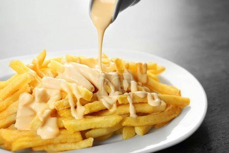 Pouring cheese sauce on french fries