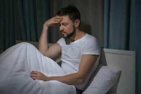 Photo for Handsome young man suffering from headache while resting in bed at night - Royalty Free Image