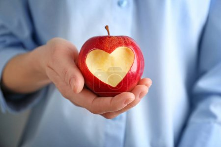 Photo for Woman hand holding fresh red apple with heart-shaped cut out, closeup - Royalty Free Image