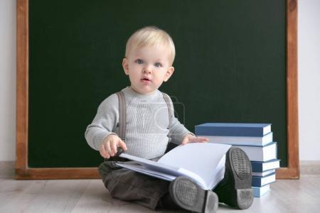 Photo pour Mignon petit garçon avec des livres assis sur le sol près du tableau noir - image libre de droit