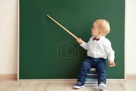 Photo pour Petit garçon mignon avec pointeur assis sur une pile de livres près du tableau noir - image libre de droit