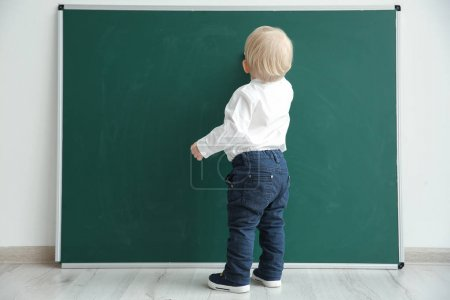 Photo pour Mignon petit garçon écriture sur tableau noir dans salle de classe - image libre de droit