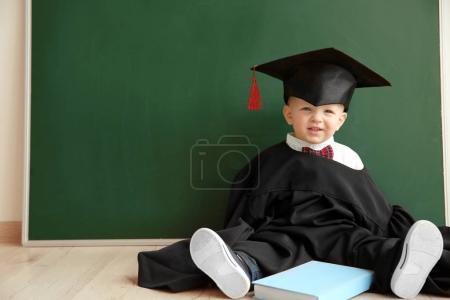 Photo pour Petit garçon mignon avec livre, chapeau magister et robe assise sur le sol près du tableau noir - image libre de droit