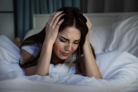 Photo for Beautiful young woman suffering from headache while lying on bed at night - Royalty Free Image