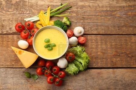 Creamy cheese in bowl and fresh vegetables