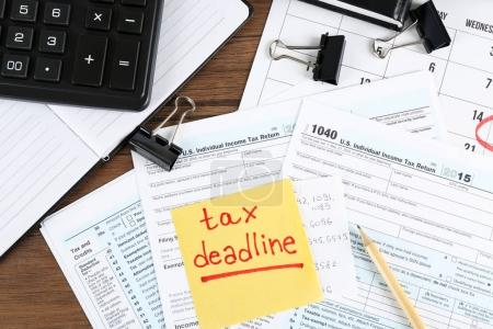 Paper sheet with text TAX DEADLINE and individual tax return form on table
