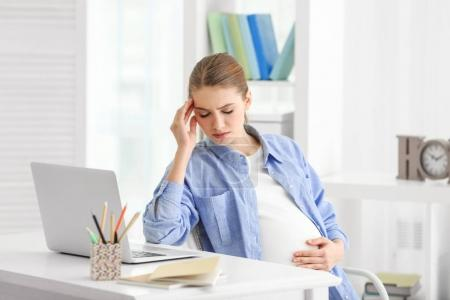 Pregnant woman suffering from headaches while sitting at workplace in light room