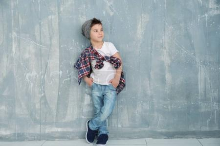 Cute stylish boy near grunge wall