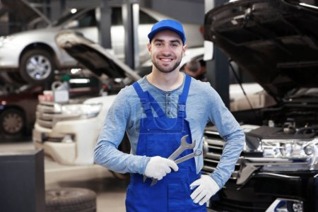 Photo for Young mechanic with tools standing in front of open car hood - Royalty Free Image