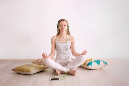 Jeune femme méditant et écouter de la musique tout en étant assis sur le plancher à la maison
