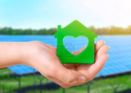 Energy savings concept. Female hand with house sha...