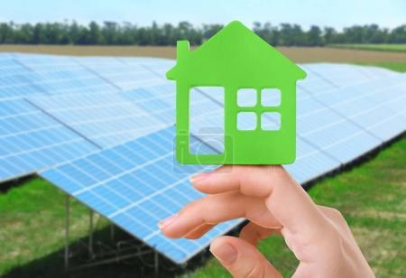 Foto de Concepto de ahorro de energía. Mano femenina con la casa en forma de figura sobre fondo de paneles solares - Imagen libre de derechos