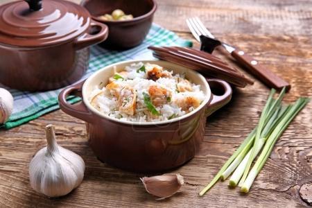 Photo pour Délicieux riz au poulet dans une casserole sur la table en bois - image libre de droit