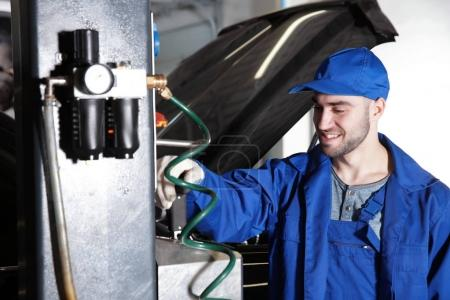 mechanic standing near auto lift