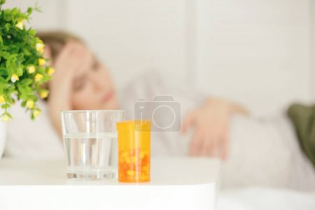 Glass of water, box with pills on table and blurred woman suffering from headache on background