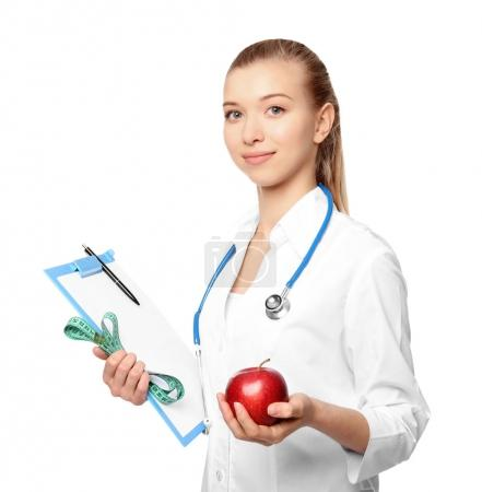 Diet concept. Female nutritionist with apple and clipboard on white background