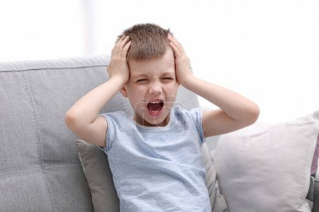 Little boy suffering from headache at home