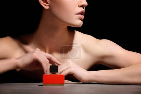 Photo for Beautiful young woman with bottle of perfume on dark background, closeup - Royalty Free Image