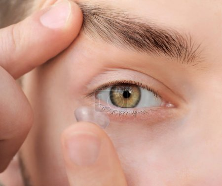 man putting contact lens