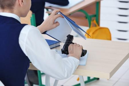 schoolboy sitting at desk with gun