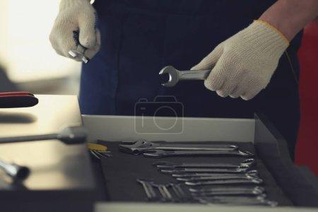 Photo pour Mécanicien automobile outils de sélection dans l'atelier de réparation automobile, gros plan - image libre de droit