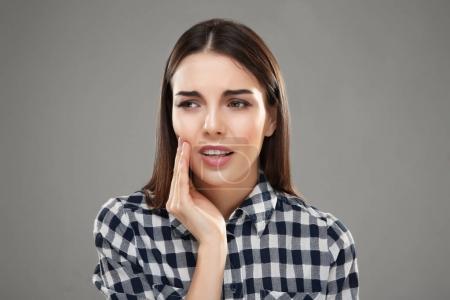 Photo pour Belle jeune femme souffrant de maux de dents sur fond gris - image libre de droit