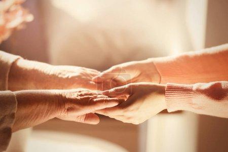 Photo pour Vieilles et jeunes femmes tenant la main sur fond flou, gros plan - image libre de droit