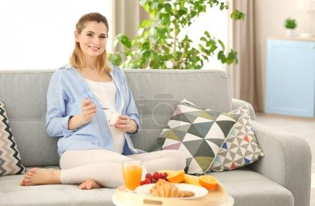Young pregnant woman having breakfast