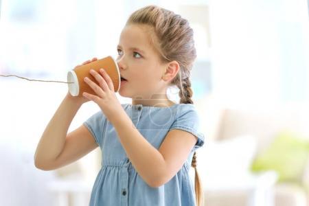 Photo pour Mignonne petite fille à l'aide de tasse en plastique comme téléphone alors qu'il jouait à la maison - image libre de droit