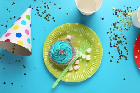 Plate with birthday cupcake and cup