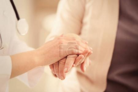 doctor holding hands of old woman