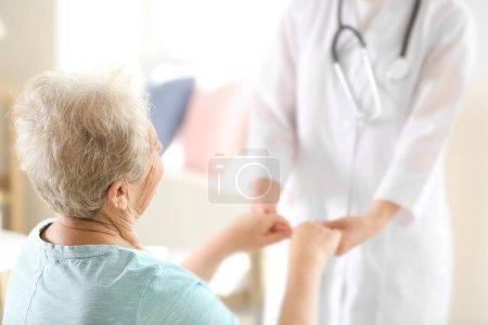 doctor holding hands of elderly woman