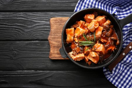 Photo for Frying pan with chicken cacciatore on kitchen table - Royalty Free Image