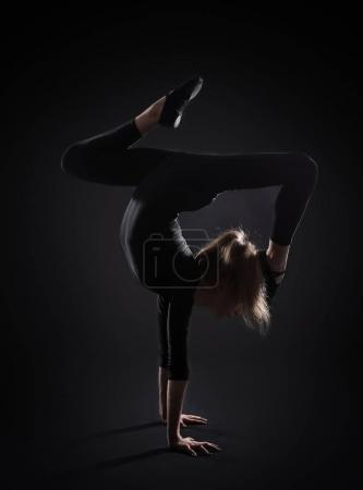 Young girl doing gymnastics on dark background