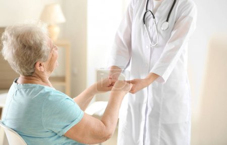 doctor holding hands of elderly woman