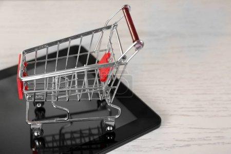 Photo pour Concept d'achat en ligne. Tablette avec mini chariot de marché sur fond en bois - image libre de droit
