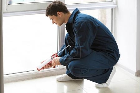 worker sealing joints of office window